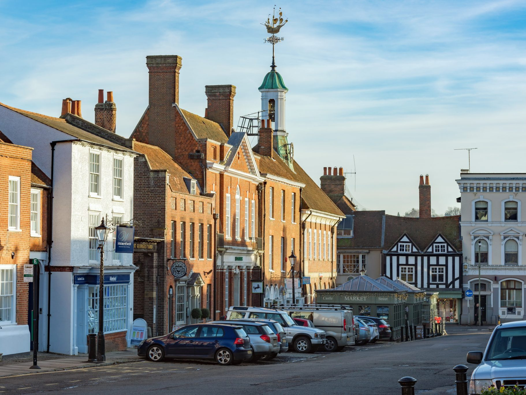 Farnham, UK. December 14th 2016. Castle Street in the centre of Farnham is an old street with a mixture of commercial and residential buildings. Cars are parked up in marked bays on the street. Shops comprise estate agencies, restaurants and specialist retail outlets.